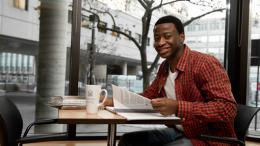 Un jeune homme assis à une table feuillette un document tout en souriant à la caméra.
