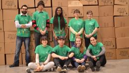 Student volunteers in green t-shirts in front of stacked boxes in a warehouse
