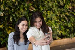 Two young women taking a selfie together on a smartphone.
