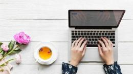 Laptop and cup of tea on a white wood background