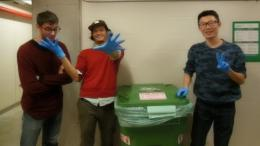 Alternative Student Break (ASB) participants acting silly next to a recycling bin