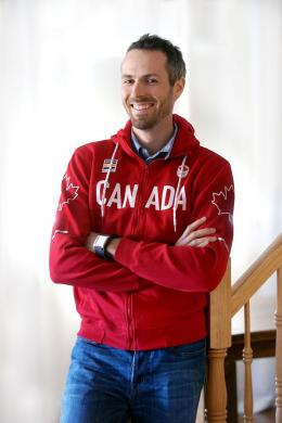 A smiling man wearing a Team Canada sweater.