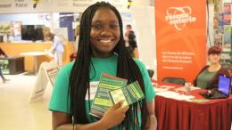 Student volunteer at the Volunteer Fair holding a pamphlets and contest ballot, standing in front of an information table for a Community Partner.