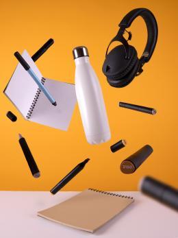 écouteurs sans fil noirs suspendus dans les airs, avec une bouteille d'eau de sport et un calepin