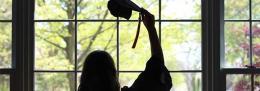 Women raising her graduation hat off her head