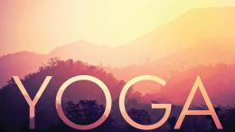 """The word """"Yoga"""" is superimposed on a picture of hills at sunset."""