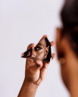 une personne se regarde à travers un miroir brisé