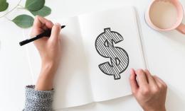 Une personne dessinant un signe de dollars dans un cahier.