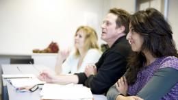 Deux femmes et un hommes dans une salle de classe