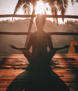 Une femme méditant au coucher du soleil