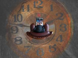 A human figure working on a computer in the middle of a giant clock.