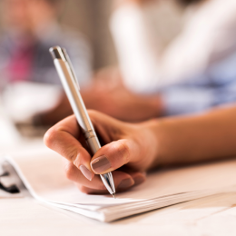 Étudiante prend des notes avec un stylo