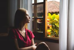 une femme assise près d'une fenêtre, l'air pensif