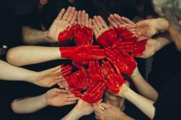 De nombreuses mains peintes de rouge, placées de façon à former un coeur.