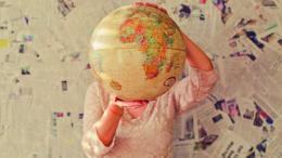 Une femme tient un globe terrestre. | A woman holds a terrestrial globe.