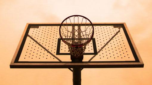 A sunset sky over a basketball hoop.
