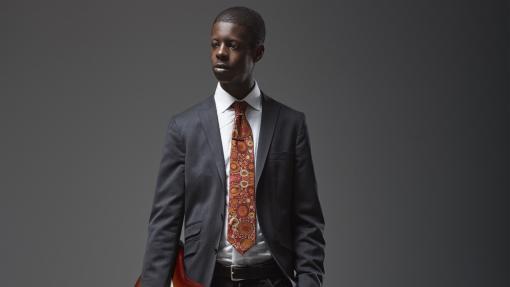 Karim Ouellet porte une cravate et se tient devant fond noir.
